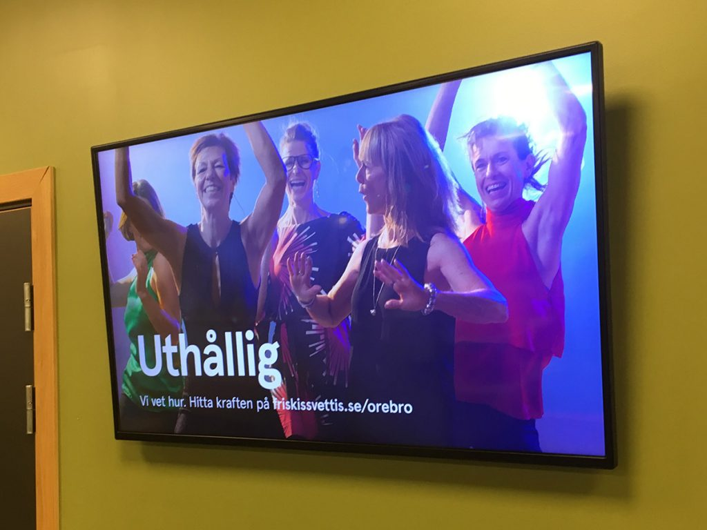 Reklambilder från fotografering åt Friskis & Svettis, informationsskärm på ett av gymmen. Foto: SHOOT IT Film & Foto i Örebro